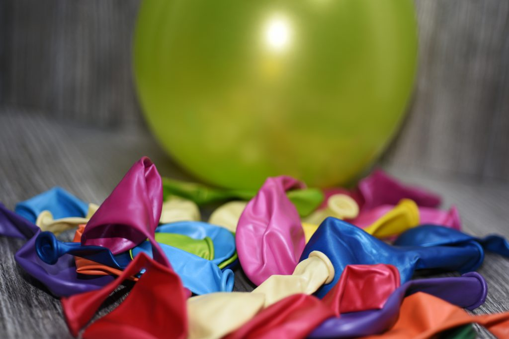 Close-up of coloured, deflated balloons on a wooden table